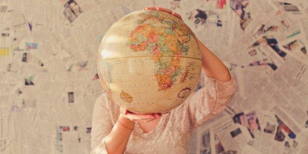 Junge Frau hält eine Weltkugel hoch