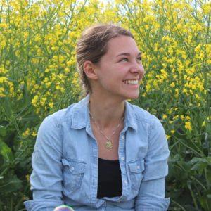 Alina lachend vor einem Rapsfeld
