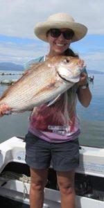 Alina steht auf einem Boot und hält einen selbst gefangenen Fisch in den Händen
