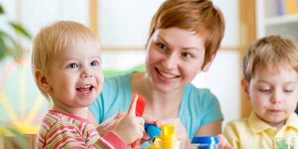 Junge Frau spielt mit zwei Kleinkindern.