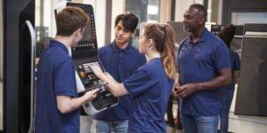 Eine Gruppe Auszubildender steht um ein Gerät