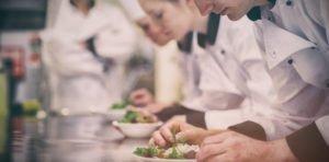Junge Koch-Auszubildende richten Teller an