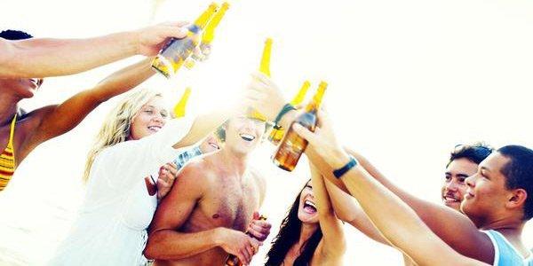 Junge Leute feiern im Sommer am Strand