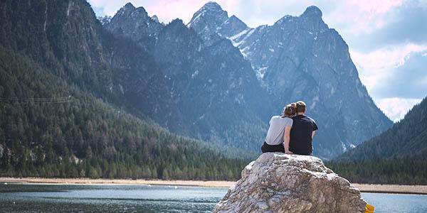 Paar sitzt auf Felsen vor Bergen