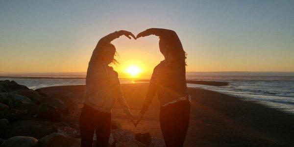Zwei junge Frauen gucken sich den Sonnenuntergang an