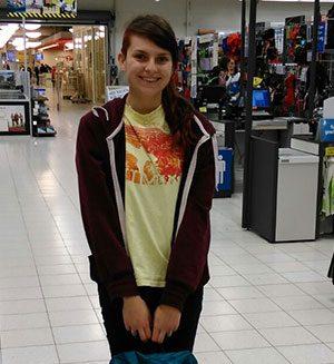 Junge Frau steht mit gepacktem Rucksack am Flughafen