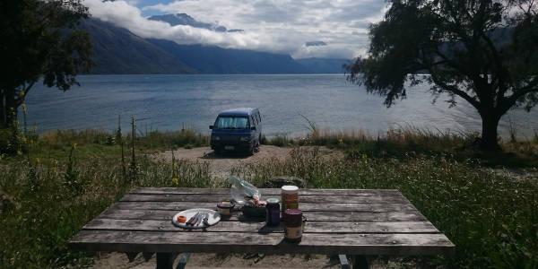 Campervan vor einem See, im Vordergrund ein Picknicktisch