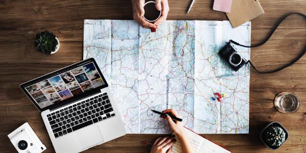 Zwei junge Leute planen mit Landkarte und Laptop eine Reiseroute