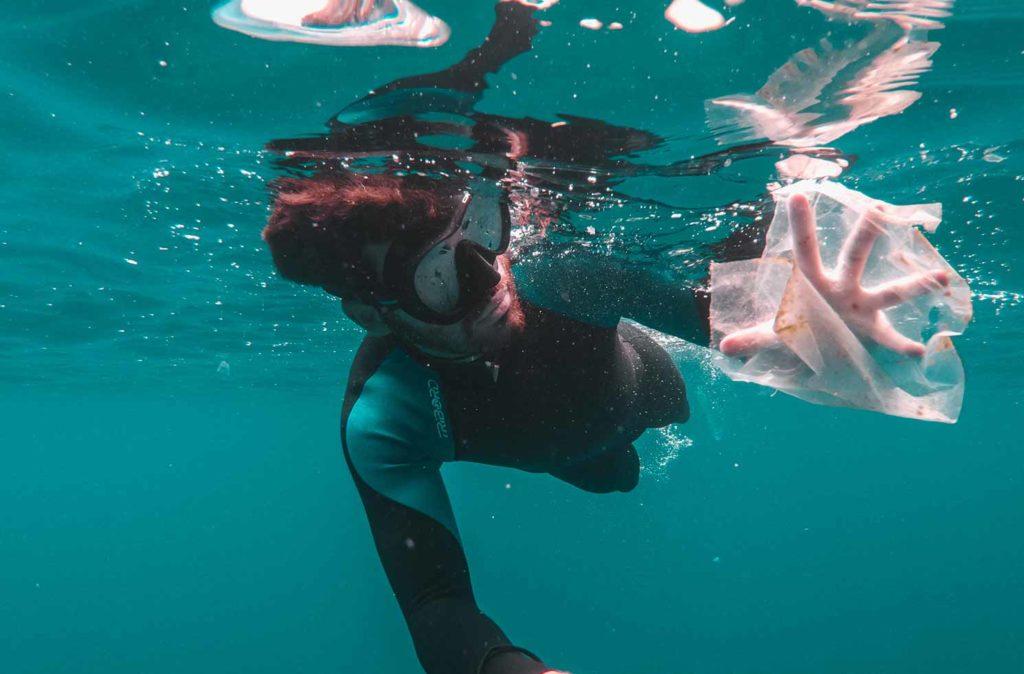 Taucher sammelt Plastik im Meer