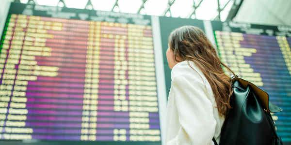 Junge Frau vor einer Anzeigetafel
