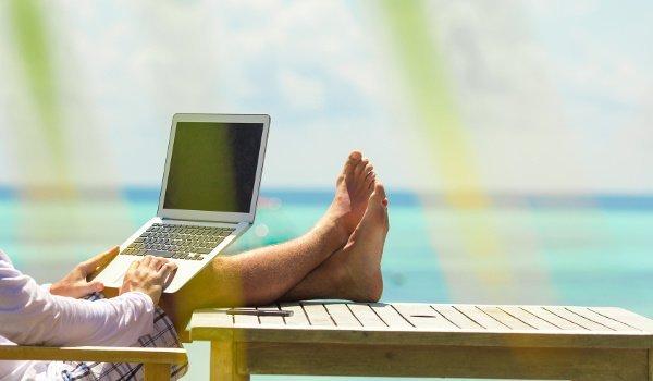 Ein Mann arbeitet am Strand mit seinem Laptop und legt die Füße hoch