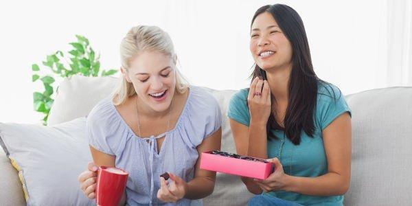 Zwei lachende junge Frauen sitzen auf einem Sofa und essen Schokolade