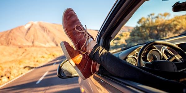 Person lässt Füße aus dem Autofenster baumeln.