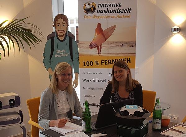 Julia und Jane beim Interview, vor dem Travelbuddy und Initiative auslandszeit Plakat