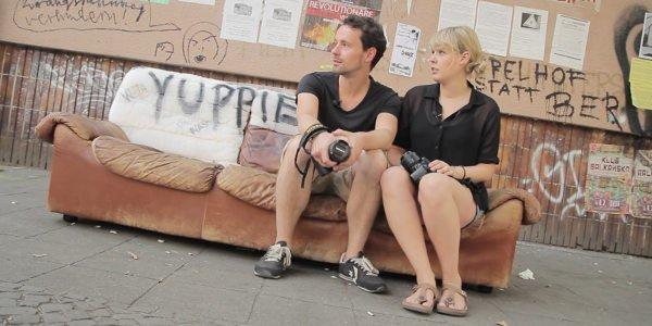 Jenny und Basti von 22places mit Kameras auf einem Sofa