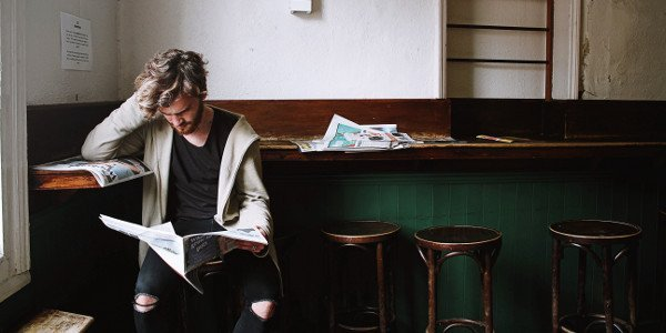 Junger Mann liest Zeitung