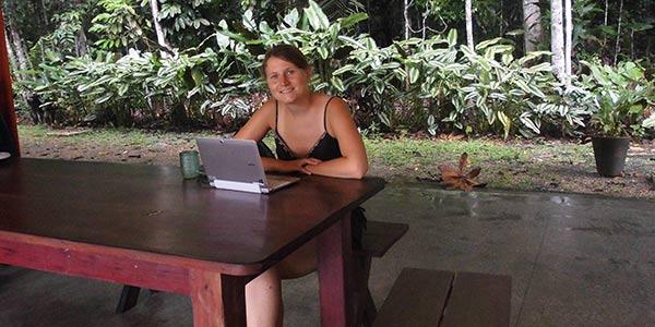 Junge Frau mit Laptop an einem Tisch
