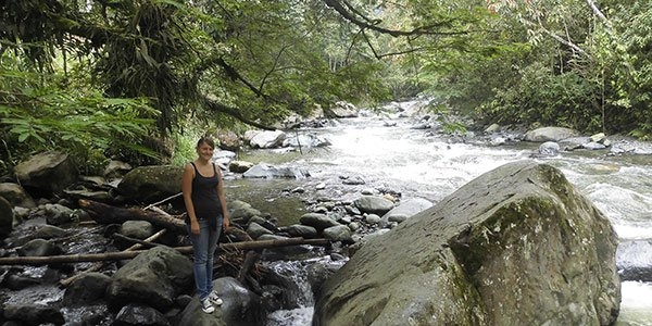 Junge Frau steht auf großen Steinen an einem Flussufer