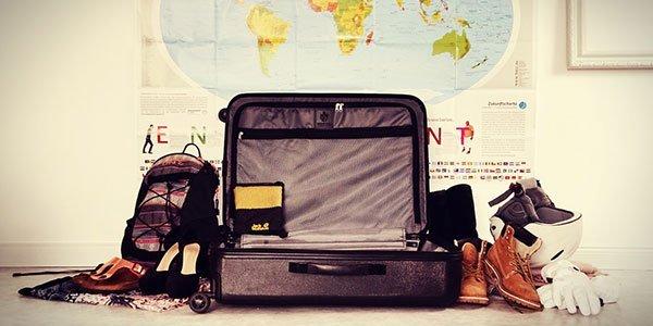 geöffneter Koffer, Rucksack und Kleidung vor einer Weltkarte
