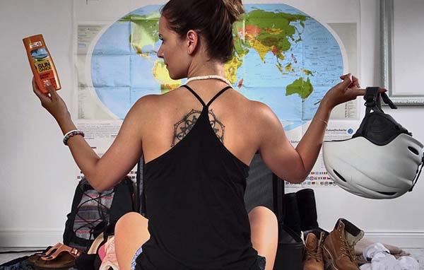 Junge Frau, sitzt mit dem Rücken zur Kamera vor einer Weltkarte, hat einen Helm und Sonnencreme in der Hand