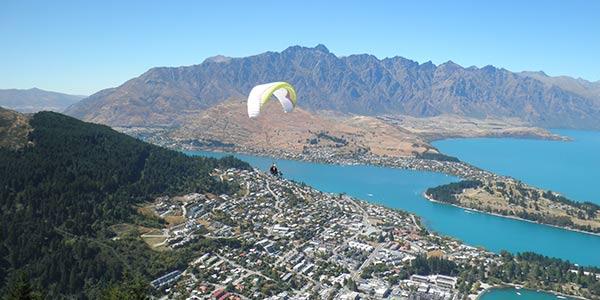 Überblick über Queenstown in Neuseeland von einem Berg aus, mit Paraglider im Vordergrund