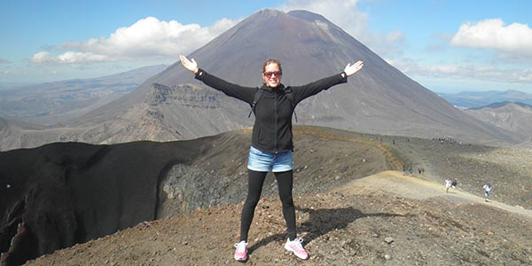 Junge Frau vor dem Panorama des Tongariro Nationalparks, im Hintergrund der Ngauruhoe Vulkan