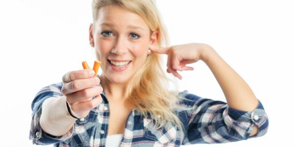 Frau mit Ohropax in einer Hand, hält sich ein Ohr zu.