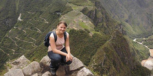 Junge Frau auf einem Berg, im Hintergrund sieht man grüne, bewachsene Berghänge