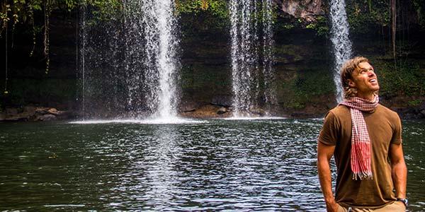 Junger Mann steht vor einem See mit Wasserfall