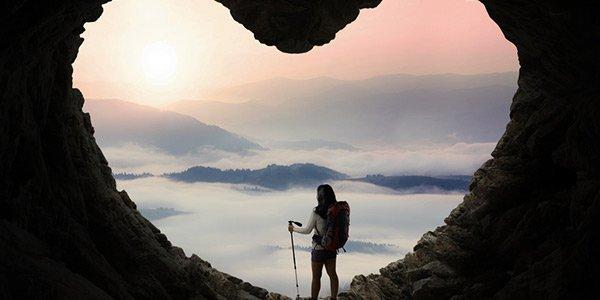 Backpackerin beobachtet Sonnenaufgang aus herzförmiger Höhle