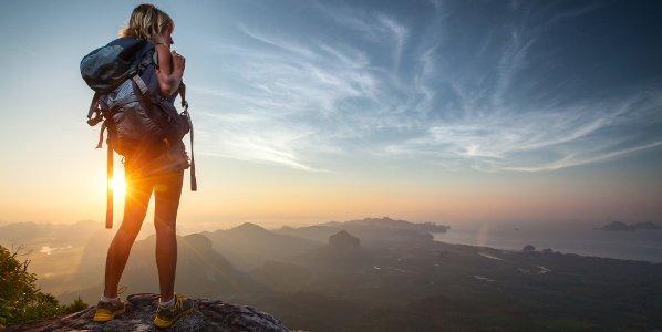 Backpackerin steht bei Sonnenaufgang auf Berggipfel und schaut aufs Meer.