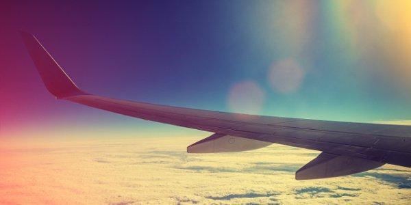 Blick aus dem Flugzeug über die Wolkendecke bei Sonnenaufgang.