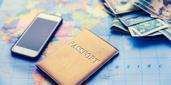 Auf einer Weltkarte liegen Smartphone, Reisepass und Geld.
