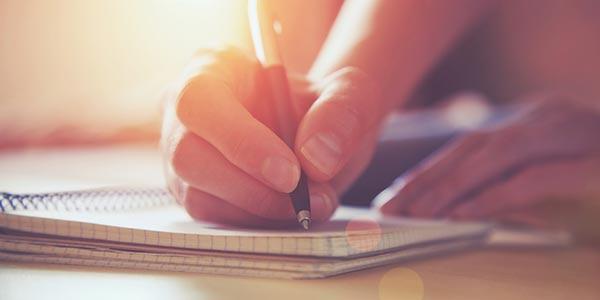 Hand mit Stift schreibt auf Notizblock.