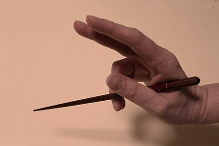 How To: Mit Stäbchen essen. Step 1: So hältst du das erste Stäbchen zwischen Ringfinger und Daumen.