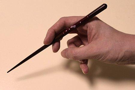 How To: Mit Stäbchen essen. Step 2: Das zweite Stäbchen hältst du mit Zeigefinger und Daumen.