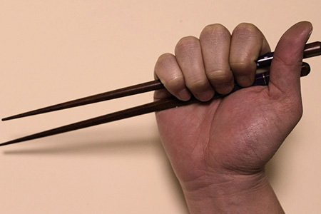 How To: Mit Stäbchen essen. So nicht. Stäbchen mit der Faust halten.