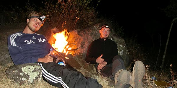Backpacker mit Stirnlampe an Lagerfeuer.
