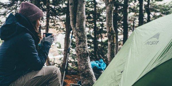 Junge Frau trinkt Kaffee vor einem Zelt
