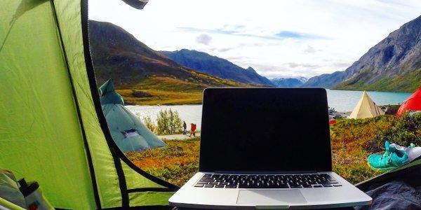 Laptop im Zelteingang und Blick auf einen See und Berge